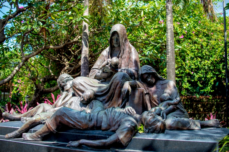 The central figure is a woman, quite large, dominant in size and proportion. She is the motherland - she weeps as she holds an infant, the symbol of hope. But the infant is dead - it represents lost hope. The female figure on the right side is a victim of rape; there is an infant clinging to her. On the left side is a man, still alive, looking confused and disoriented - despair on his face. The young boys are dead - representing the youth the coutry lost. The dead man lying in front portrays the elderly, who were caught in the battle.